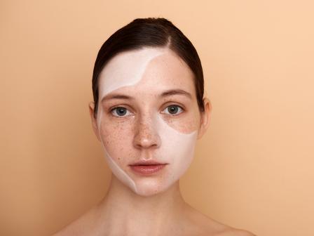 Девушка с остатками тканевой маски на лице.