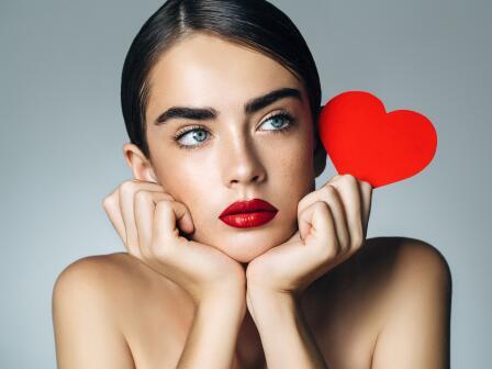 Девушка держит в руках красное сердечко