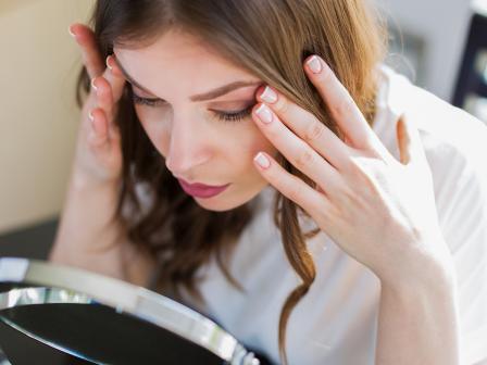 Девушка склонилась к круглому настольном зеркалу, придерживая пальцам внешние уголки глаз