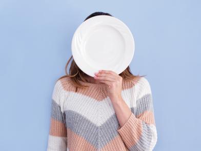 Девушка держит перед лицом белую тарелку, лицо не видно