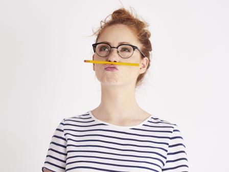 Рыжеволосая девушка в очках и полосатой футболке задумалась, держит под носом карандаш