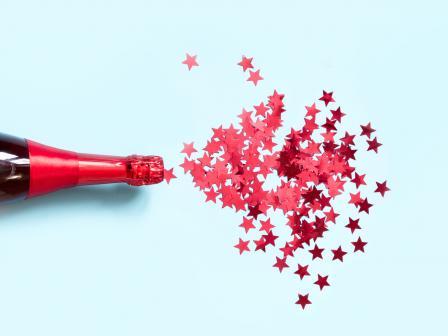 Из бутылки с шампанским вылетают конфетти в виде блестящих розовых звездочек