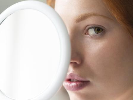 Девушка прикрывает лицо зеркалом
