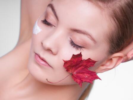 Девушка с закрытыми глазами, кремом на одной щеке осенним листом – на другой.
