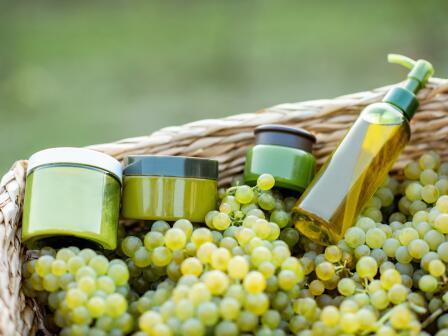 Косметика в зеленой упаковке на гроздьях зелёного винограда в корзине