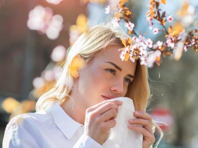 девушка-аллергик в белой блузе и с белым платком у цветущего дерева
