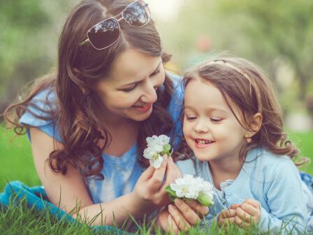 мама и дочка на зеленой траве с цветами яблони