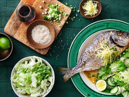 блюдо из рыбы и салат на темно-зеленом деревянном столе аллергены