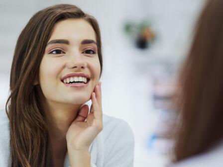 темноволоса девушка с гладкой чистой ухоженной кожей смотрится в зеркало