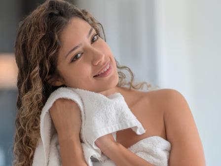 девушка улыбается и вытирает лицо белым полотенцем