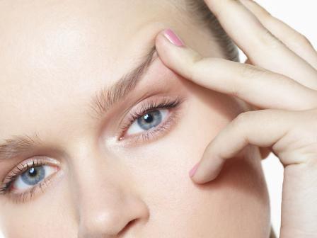 сероглазая девушка трогает кожу лица поднимает бровь