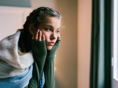 девушка с ухоженной кожей очень расстроена и смотрит в окно