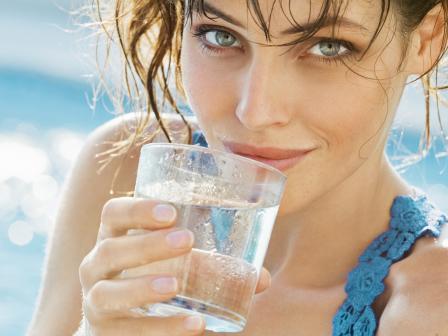 девушка с ухоженной кожей пьет воду из стакана на фоне воды