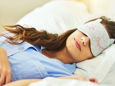 Темноволосая девушка в голубой пижаме и маске-совушке спит, улыбаясь, на белоснежном белье