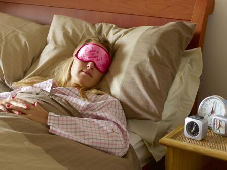 Девушка спит в розовой маске, на тумбочке рядом стоит много будильников