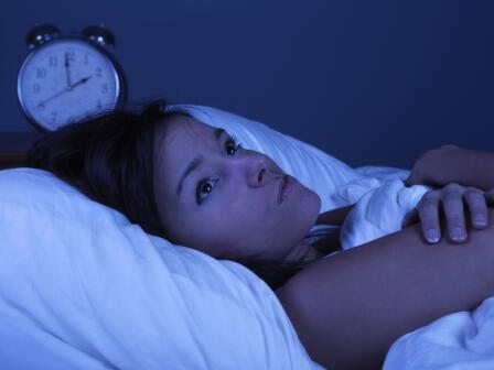 Девушка лежит на кровати, проснувшись ночью