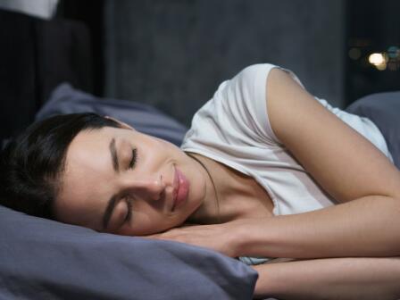Девушка спит, улыбаясь, на кровати с темным постельным бельем