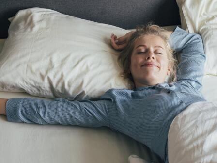 Светловолосая девушка в голубой пижаме счастливо спит