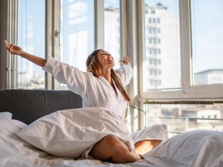 Девушка, проснувшись, счастливо потягивается в постели на фоне городского пейзажа за окном