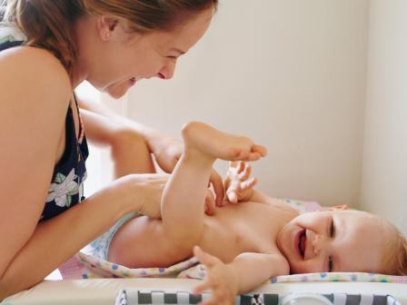 Мама меняет младенцу подгузник.
