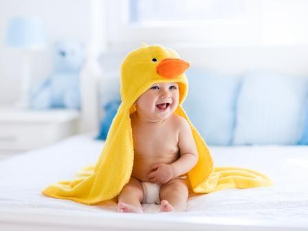 Жизнерадостный младенец со здоровой кожей в желтом банном халате