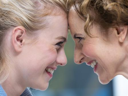 Улыбающиеся мама и дочка в профиль