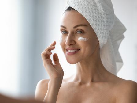 Ухоженная женщина в банном тюрбане наносит крем на лицо