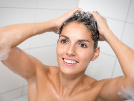 Девушка моет голову шампунем для волос