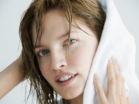 Девушка растирает мокрые волосы полотенцем