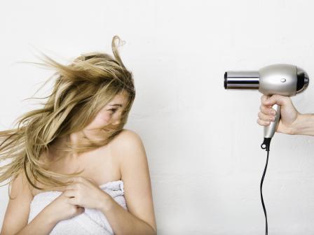 Девушка стоит под струей горячего воздуха фена
